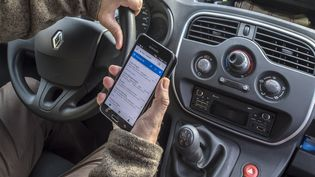 Un automobiliste utilise son téléphone portable derrière le volant, en Belgique, le 17 novembre 2017. (PHILIPPE CL?MENT / BELGA MAG / AFP)