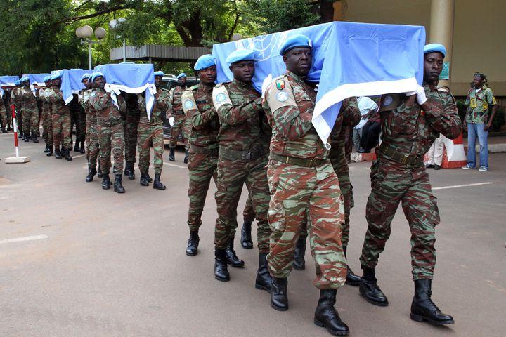 Des soldats nigériens de la Minusma portent les cercueilsaux couleurs de l'ONUde neufs soldats à Bamako, le 7 octobre 2014. (HABIBOU KOUYATE / AFP)