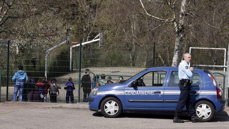 Un gendarme est en poste devant l'école Le Mas de la Raz de Villefontaine (Isère), où un directeur d'école soupçonné de pédophilie a été arrêté, le 24 mars 2015. (PHILIPPE DESMAZES / AFP)