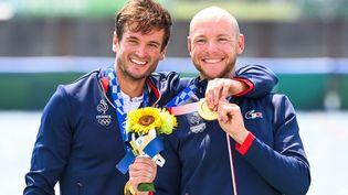 Les sourires de Hugo Boucheronet Matthieu Androdias sur le podium après leur victoire en aviron deux de couple, le 28 juillet à Tokyo. (CHARLY TRIBALLEAU / AFP)