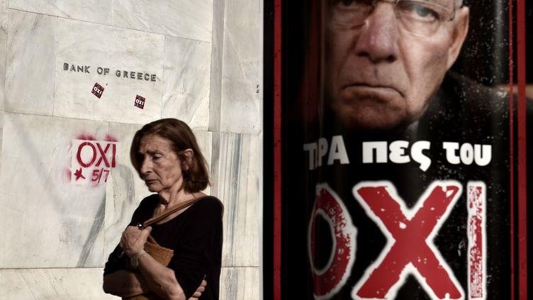 Une femme passe devant le siège de la Banque de Grèce, le 3 juillet 2015, non loin d'une affiche invitant à voter non au référendum prévu deux jours plus tard. (ARIS MESSINIS / AFP)