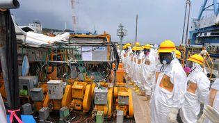 Des experts et des élus inspectent les installations censées contenir les fuites d'eau radioactives, le 6 août 2013, à la centrale nucléaire de Fukushima (Japon). (JAPAN POOL / JIJI PRESS / AFP)