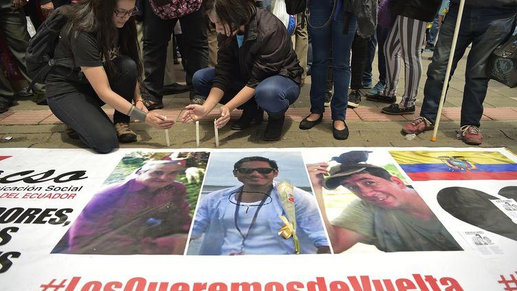 Des proches des journalistes Javier Ortega, Paul Rivas et de leur chauffeur Efrain Segarra allument des bougies, près de leurs photos, à Quito (Equateur), le 13 avril 2018. (RODRIGO BUENDIA / AFP)