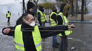 """Un membre des """"giles jaunes"""" armé d'une fronde fait face aux forces de l'ordre près des Champs-Elysées à Paris le samedi 1er décembre 2018. (LUCAS BARIOULET / AFP)"""