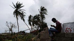 Un homme consulte son téléphone portable au milieu des ruines de sa maison détruite par l'ouragan Matthew, aux Cayes (Haïti), le 5 octobre 2016. (ANDRES MARTINEZ CASARES / REUTERS)