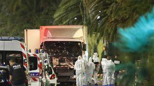 La police scientifique se tient à côté du camion qui a foncé dans la foule sur la promenade des Anglais à Nice (Alpes-Maritimes), le 15 juillet 2016. (ERIC GAILLARD / REUTERS)