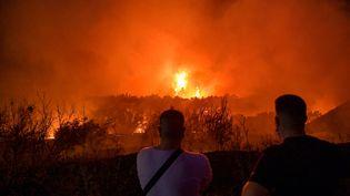 Des personnes regardent le feu se déployer à Tatoi, près d'Athènes, en Grèce, le 3 août 2021. (MILOS BICANSKI / GETTY IMAGES EUROPE)