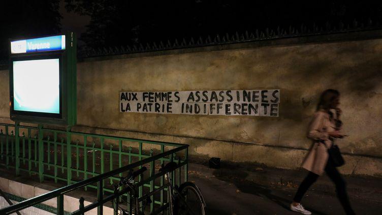 """Un groupe qui dénonce les féminicides à coller ce message """"Aux femmes assassinées, la patrie indifférente"""" près du métro Varennes (7e arrondissement de Paris) vendredi 6 septembre. (LUDOVIC MARIN / AFP)"""