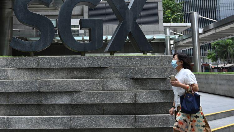 Une femme masquée passe devant la bourse de Singapour, le 7 avril 2020. (ROSLAN RAHMAN / AFP)