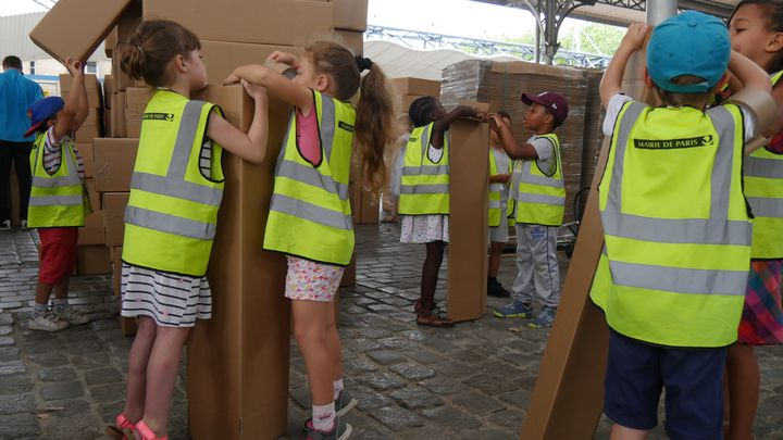 Des enfants aident à assembler les cartons, mercredi 19 juillet  (Elise Koutnouyan / Culturebox)