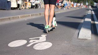 Un utilisateur de trottinette électrique en libre service circule sur une piste cyclable, à Paris. (AURÉLIEN ACCART / RADIO FRANCE)