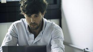 Un jeune homme consulte son ordinateur. Photo d'illustration. (ERIC AUDRAS / MAXPPP)