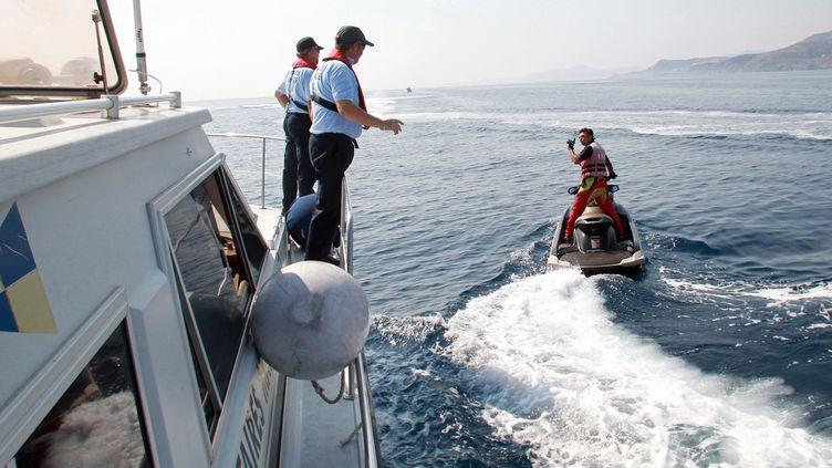 Des agents de la direction départementale des territoires et de la mer (DDTM) effectuent un contrôle en mer auprès d'un conducteur de scooter des mers au large de Perpignan, le 12 juillet 2013. (RAYMOND ROIG / AFP)
