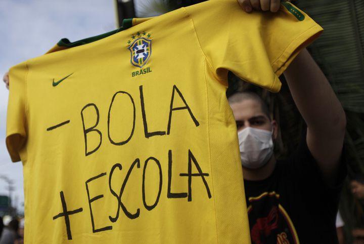 """""""Moins de ballon, plus d'école"""", peut-on lire sur un maillot de l'équipe brésilienne tenu par un manifestant, le 20 juin 2013, à Recife (Brésil). (RICARDO MORAES / REUTERS)"""