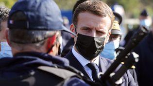 Emmanuel Macron échangeant avec un policier, le 5 novembre 2020. (GUILLAUME HORCAJUELO / POOL)