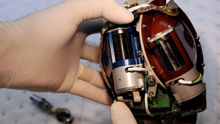 Un employé de la société Carmat inspecte un cœur artificiel, le 24 septembre 2009, à Velizy, près de Paris. (FRANCK FIFE / AFP)