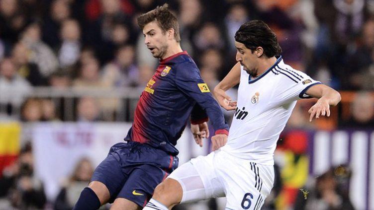 Gérard Piqué (FC Barcelone) et Sami Khedira (Real Madrid) à la lutte (PIERRE-PHILIPPE MARCOU / AFP)