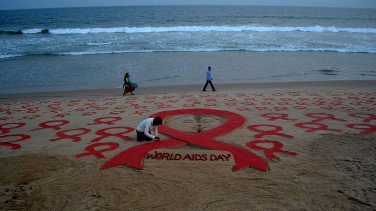 Des logos symbolisant la lutte contre le Sida sont installés sur une plage à Bhubaneswar (Inde), le 1er décembre 2016. (NURPHOTO / AFP)