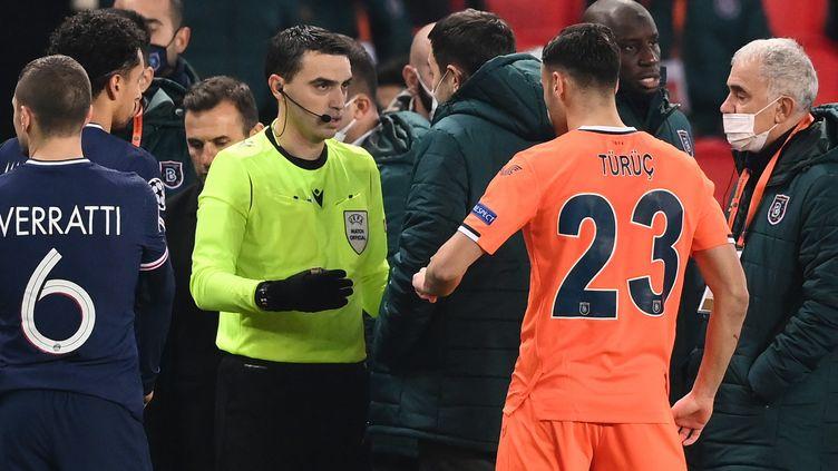 L'arbitre roumain OvidiuHategan discute avec le joueur du Basaksehir Istanbul, Demba Ba après la suspension du match contre le PSG, mardi 8 décembre 2020. (FRANCK FIFE / AFP)