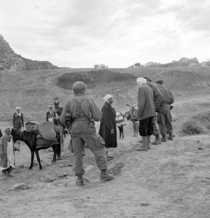 Des parachutistes français en patrouille dans le massif de l'Aurès, ont arrêté une caravane et interrogent les paysans algériens, le 12 novembre 1954, dix jours après la série d'attentats qui a marqué le début de la guerre d'indépencance algérienne. (Pierre Bonnin / INTERCONTINENTALE / AFP )