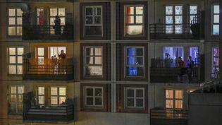 Habitants applaudissant les soignants à leur balcon, pendant le confinement, à Montreuil. (REMI DECOSTER / HANS LUCAS / AFP)
