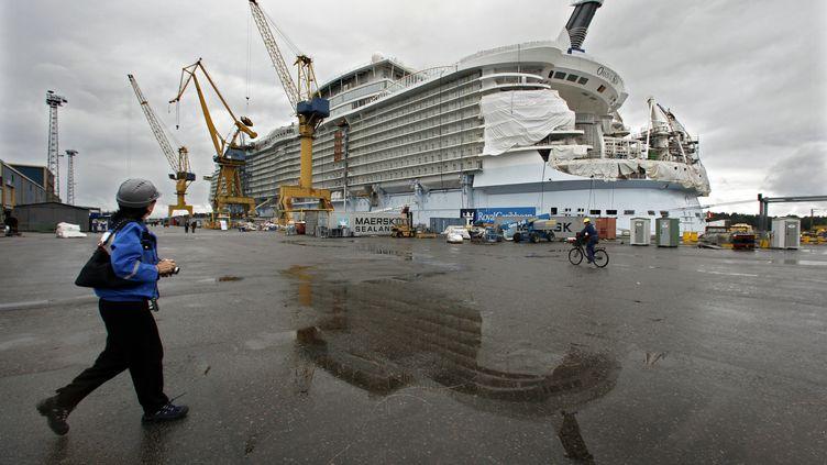 Un visiteur observe le Oasis of the Seas, lors de construction sur les chantiers navals finlandais STX de Turku, le 27 août 2009. (BOB STRONG / REUTERS)
