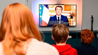 Une famille devant le discours d'Emmanuel Macron, lundi 17 mars. (photo d'illustration) (Damien Meyer / AFP)