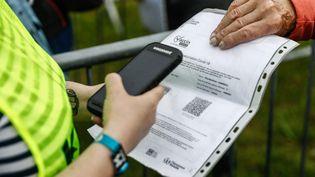 Un spectateur qui va assister au festival des Vieilles Charruesmontre son pass sanitaire à l'entrée àCarhaix-Plouguer (Finistère), le 8 juillet 2021. (SAMEER AL-DOUMY / AFP)