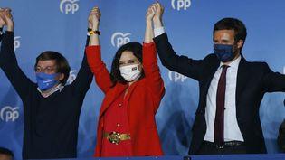 Madrid, le 4 mai 2021. Isabel Diaz Ayuso, au centre, la candidate du Parti Populaire, victorieuse aux élections régionales du 4 mai, Pablo Casado, le leader du PP, à droite, et le maire de Madrid, Jose Luis Martinez Almeida, à gauche. (SENHAN BOLELLI / ANADOLU AGENCY / AFP)