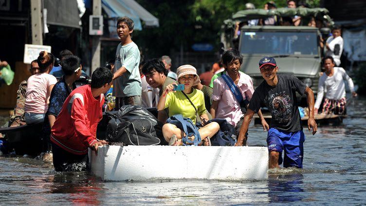 Scène de la vie quotidienne dans les rues inondées de Bangkok (Thaïlande), le 31 octobre 2011. (PORNCHAI KITTIWONGSAKUL / AFP)