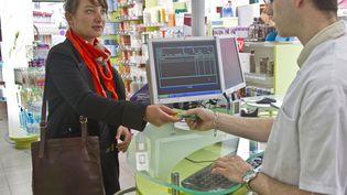 Une cliente tend sa carte Vitale pour la prise en charge de ses médicaments dans une pharmacie, le 16 décembre 2010. (HERVÉ DE GUELTZL / PHOTONONSTOP/AFP)