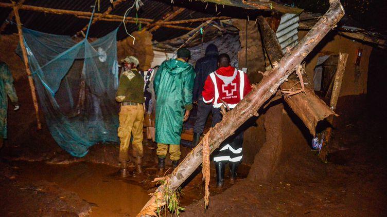 Des volontaires rechechent des survivants, dans une zone résidentielle, après la rupture d'un barrage à Solai, au Kenya, le 10 mai 2018. (AFP)