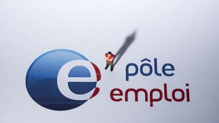 Une figurine à proximité du logo Pôle Emploi, photographiée le 27 août 2018 à Paris. (JOEL SAGET / AFP)