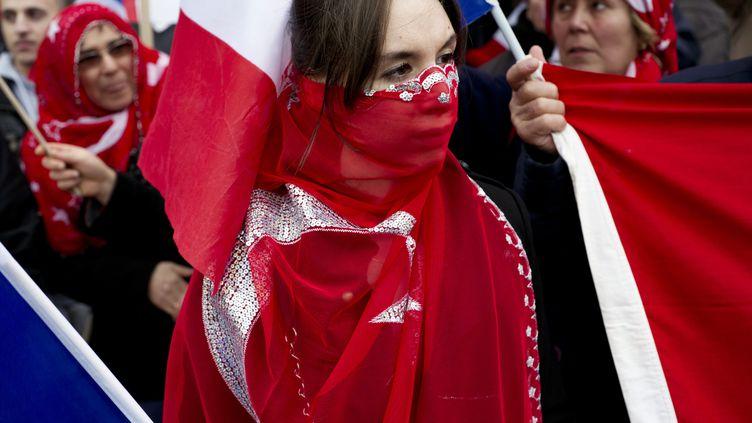Entourée d'un drapeau turc, une jeune femme manifeste contre la proposition de loi visant à pénaliser la négation des génocides, à proximité du Sénat, à Paris, le 23 janvier 2012. (FRED DUFOUR / AFP)