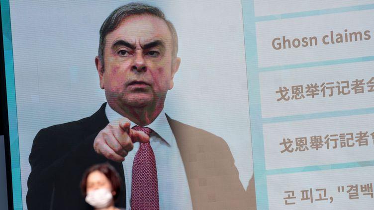 Un écran montrant Carlos Ghosn, l'ancien président de Nissan, à Tokyo, le 9 janvier 2020. (BEHROUZ MEHRI / AFP)