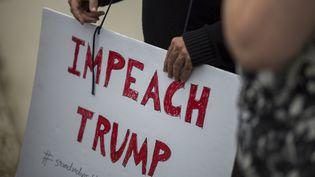 Un manifestant tient une pancarte pour demander la destitution de Donald Trump, le 10 mai 2017 à Los Angeles (Californie) aux Etats-Unis. (DAVID MCNEW / AFP)