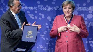 La chancelière allemande Angela Merkel reçoit une médaille de Tedros Adhanom Ghebreyesus, directeur général de l'OMS, lors de la cérémonie d'inauguration du centre de recherche et détection des épidémies à Berlin, le 1er septembre 2021. (MICHAEL SOHN / AP / AFP)