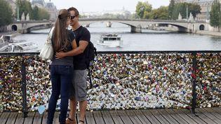 Deux amoureux sur lepont des Arts, à Paris, le 30 août 2013. (PATRICK KOVARIK / AFP)