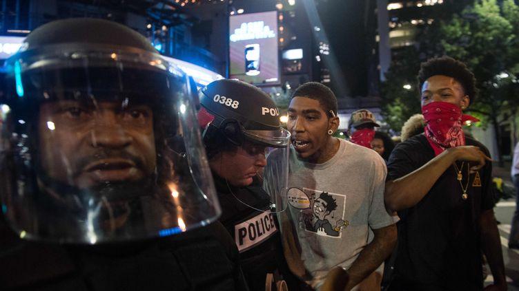 De jeunes hommes interpellent des policiers, à Charlotte (Caroline du Nord), mercredi 22 septembre 2016. (NICHOLAS KAMM / AFP)