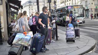 Des personnes transportent des valises dans le quartier du Marais, à Paris, le 19 octobre 2019. (SERGE ATTAL / AFP)