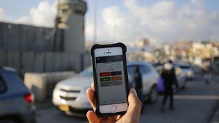A Ramallah, un palestinien utilise l'application Azmeh sur son smartphone, une application développée pour aider à la navigation des automobilistes, en février 2016. (ABBAS MOMANI / AFP)