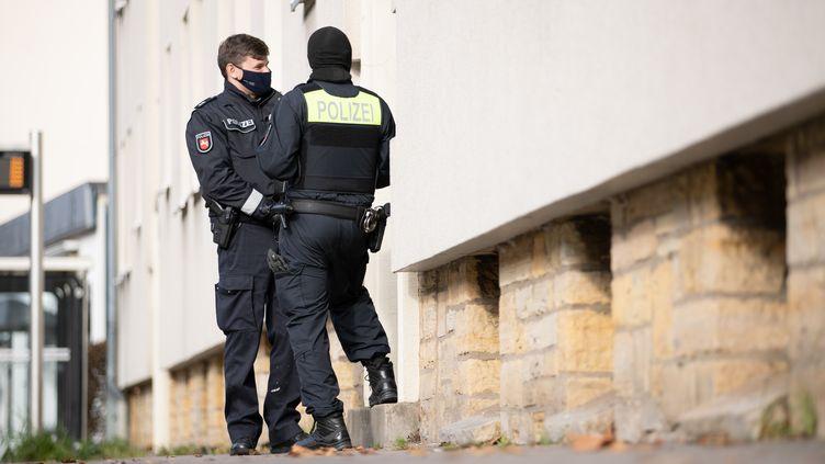 Des policiers se tiennent devant l'un des locaux perquisitionnés, à Osnabrück (Allemagne), le 6 novembre 2020. (FRISO GENTSCH / DPA / AFP)