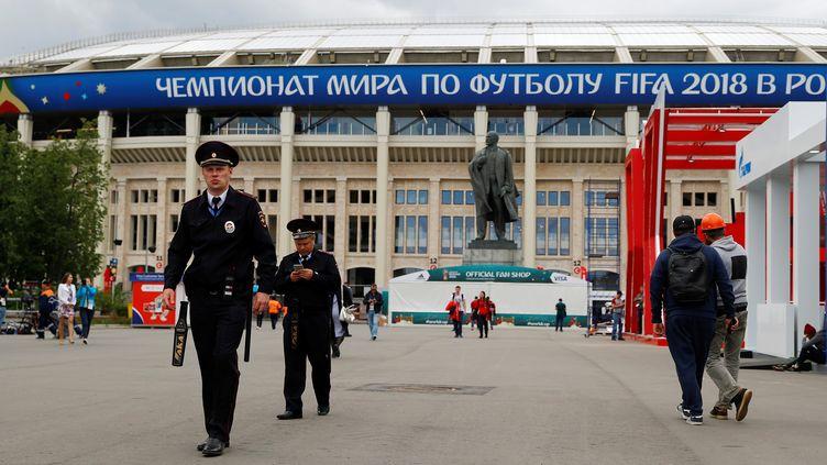 Des policiers, le 13 juin 2018, devant le stade Loujniki de Moscou, un de ceux qui accueilleront la Coupe du Monde de football. (KAI PFAFFENBACH / REUTERS)