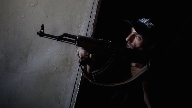 Un rebelle syrien observe des positions pro-régime à Alep (Syrie), le 9 juillet 2013. (JM LOPEZ / AFP)