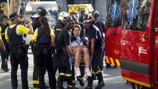 La police catalane et les services d'urgence déplacent un homme blessé après l'attaque terroriste sur La Rambla, à Barcelone (Catalogne, Espagne), le 17 août 2017. (QUIQUE GARCIA/EFE/SIPA / EFE)