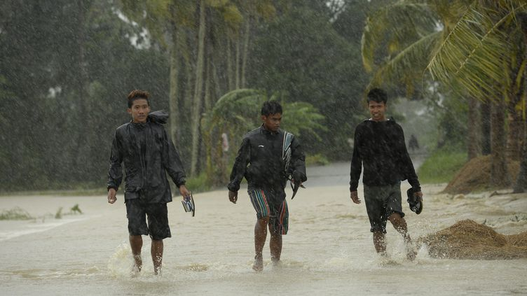 Des habitants de la ville d'Ineangan (Philippines) traversent une rue inondée lors du passage du typhon Koppu, le 18 octobre 2015. ( AFP )