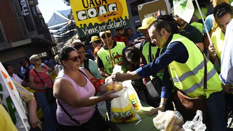 La Coordination des organisations d'agriculteurs et d'éleveurs (COAG) partage fruits et légumes avec la population de Madrid le 5 septembre 2014 (PIERRE-PHILIPPE MARCOU / AFP)