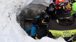 Les pompiers italiens extraient un enfant des décombres de l'hôtel dévasté par une avalanche, le 20 janvier 2017 près de Farindola (Italie). (VIGILI DEL FUOCO / AFP)