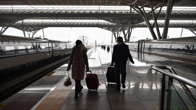 Des voyageurs sur un quai presque vide de la gare de Wuhan (Chine), le 23 janvier 2020. (HECTOR RETAMAL / AFP)