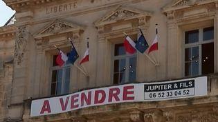 """À Frontignan, dans l'Hérault, le maire de la ville a accroché une banderole """"à vendre"""" sur l'hôtel de ville pour protester contre les coupes budgétaires du gouvernement. (FRANCE 3)"""